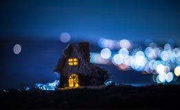 Litet dekorativt hus, härlig festlig stilleben, gulligt litet hus på natten, bakgrund för bokeh för nattstad verklig, lycklig vin arkivfoton
