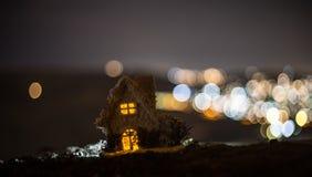 Litet dekorativt hus, härlig festlig stilleben, gulligt litet hus på natten, bakgrund för bokeh för nattstad verklig, lycklig vin arkivbilder