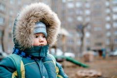 Litet en-år-gammalt barn i en huv med päls och halsduken på lekplatsen arkivfoto