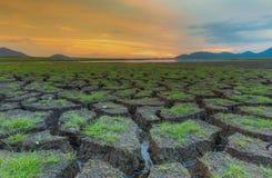 Litet exponeringsglas över knäppningland med dramatisk solnedgånghorisont Arkivfoton