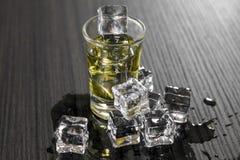 Litet exponeringsglas av den starka alkoholdrinken med iskuber royaltyfria foton