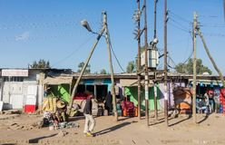 Litet färgrikt shoppar på en grusväg med några informella affärsmän arkivfoton