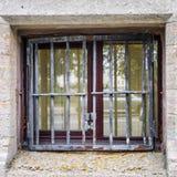 Litet fönster från källaren bak stängerna arkivfoto