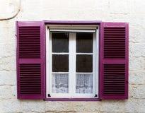 Litet fönster med purpurfärgade slutare Arkivbild
