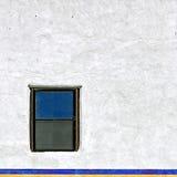 Litet fönster på den vita väggen Arkivfoto