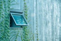 Litet fönster på väggbyggnad med ljus lutning Royaltyfri Bild