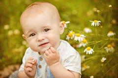 Litet förtjusande behandla som ett barn pojken med stora ögon som sitter i ett fält med D Royaltyfri Bild