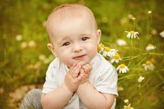 Litet förtjusande behandla som ett barn pojken med stora ögon som sitter i ett fält med D Fotografering för Bildbyråer