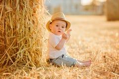 Litet förtjusande behandla som ett barn pojken med stora bruna ögon i en hatt sitter i a Arkivbild