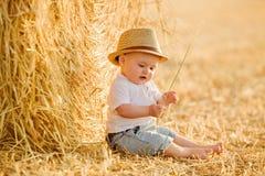 Litet förtjusande behandla som ett barn pojken med stora bruna ögon i en hatt sitter i a Arkivfoto