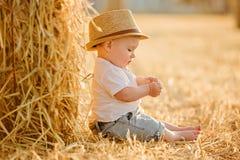 Litet förtjusande behandla som ett barn pojken med stora bruna ögon i en hatt sitter i a Royaltyfria Bilder