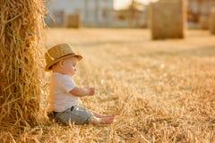 Litet förtjusande behandla som ett barn pojken med stora bruna ögon i en hatt sitter i a Royaltyfria Foton