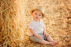 Litet förtjusande behandla som ett barn pojken med stora bruna ögon i en hatt sitter i a Royaltyfri Bild