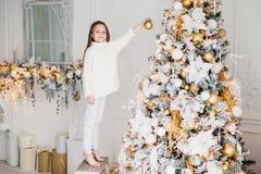 Litet förtjusande kvinnligt barn i vita tröja- och byxahåll arkivfoton
