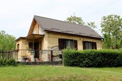 Litet familjhus med förfallet utomhus- som omges med gräs och träd royaltyfri foto