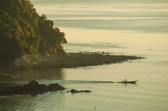 Litet fartyg för kontur av kusten i dimmig morgon för soluppgångljus Arkivbilder