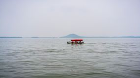 Litet fartyg för traditionell kines i Wuhan stadsDonghu den östliga sjön och Moshan kulle i Kina royaltyfri bild