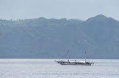 Litet fartyg i lugna vatten på en bakgrund av stora kullar Singapore Fotografering för Bildbyråer