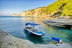 Litet fartyg med klippor runt om det - Korfu, Grekland Arkivbilder