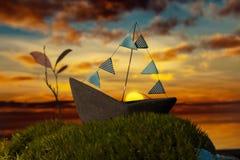 Litet fartyg på mossan på solnedgången Arkivbilder