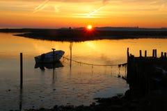 Litet fartyg som förtöjas till bron på solnedgången Royaltyfri Bild