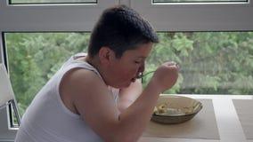 Litet fett pojkesammanträde nära fönstret och äter läcker mat begreppsbarndomfetma arkivfilmer
