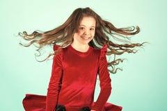 Litet flickaleende med flyghår på blå bakgrund, mode royaltyfri foto