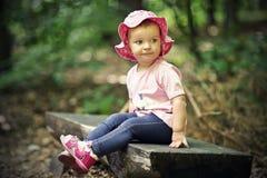 Litet flickasammanträde på bänk Royaltyfria Bilder