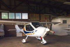 Litet flygplan i en hangar Arkivfoto