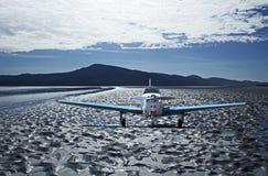 Litet flygplan på den tungt texturerade stranden Arkivfoto