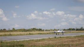 Litet flygplan på landningsbanan som flyger Arkivfoto