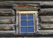 Litet gammalt fönster med exponeringsglas med en blå himmel på bakgrunden av träväggen av bygdjournalhuset Arkivfoton