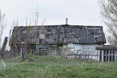 Litet gammalt f?rfallet hus med ett gistet tak royaltyfria bilder