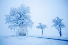 Litet gammalt kapell och gammalt träd med rimfrost och snö, dimmig juldag nära vägen under vinter Blå vintermorgon med snö Arkivbild