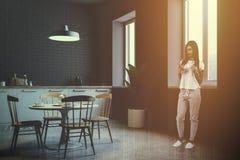 Litet grått tegelstenkökhörn, tonad kvinna Fotografering för Bildbyråer