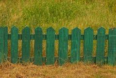 Litet grönt dekorativt trästaket i högväxt gräs arkivfoto