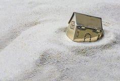 Litet guld- modellhus som sjunker in i sanden, begrepp av risken Arkivbild