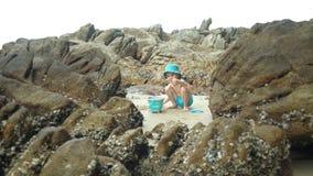 Litet gulligt barn som spelar med sand på bakgrunden av stenar med skal lager videofilmer