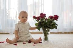 Litet gulligt behandla som ett barn litet barnpojken som sitter med rosor för mamma Arkivfoton