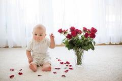 Litet gulligt behandla som ett barn litet barnpojken som sitter med rosor för mamma Royaltyfri Fotografi