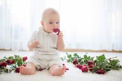 Litet gulligt behandla som ett barn litet barnpojken som sitter med rosor för mamma Royaltyfria Bilder