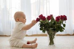 Litet gulligt behandla som ett barn litet barnpojken som sitter med rosor för mamma Fotografering för Bildbyråer