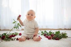 Litet gulligt behandla som ett barn litet barnpojken som sitter med rosor för mamma Arkivfoto