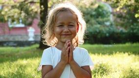 Litet gulligt behandla som ett barn flickan mediterar på gräset på grön sommar parkerar lager videofilmer