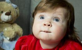 Litet gulligt behandla som ett barn med leksaker Arkivfoto