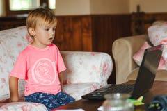 Litet gulligt hålla ögonen på för pojke favorit- tecknade filmer på bärbara datorn hemma arkivfoton