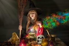 Litet gulligt pass för halloween häxaläsning ovanför krukan Arkivfoton