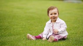Litet härligt nätt behandla som ett barn-flicka sammanträde på det gröna gräset i stad-parkera stock video