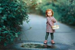 Litet härligt rödhårigt liten flickaanseende nära en pöl w royaltyfri foto