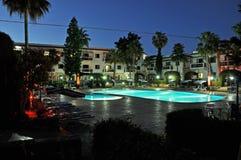 Litet hotell med simbassängen på natten Arkivbild